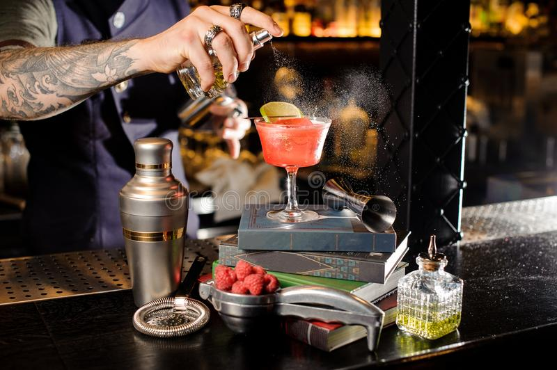 Barman spraying peat bitter on a glass with red sweet summer cocktail arranged on books. On the bar counter stock image