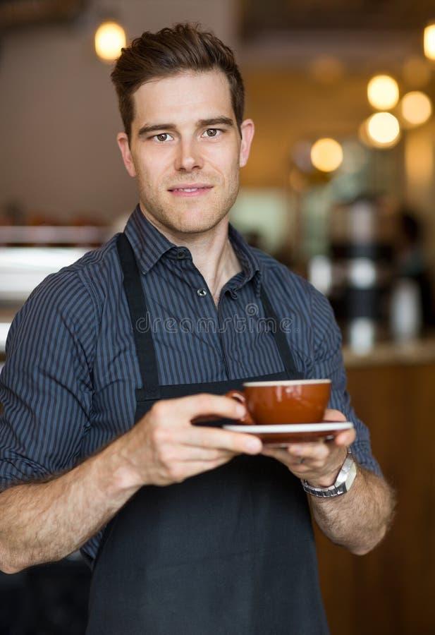 Barman Standing en café avec la tasse images libres de droits