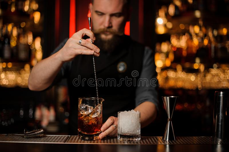 Barman stirring a delicious brown cocktail with a steel spoon in the measuring glass cup. On the bar counter in the dark blurred background royalty free stock image