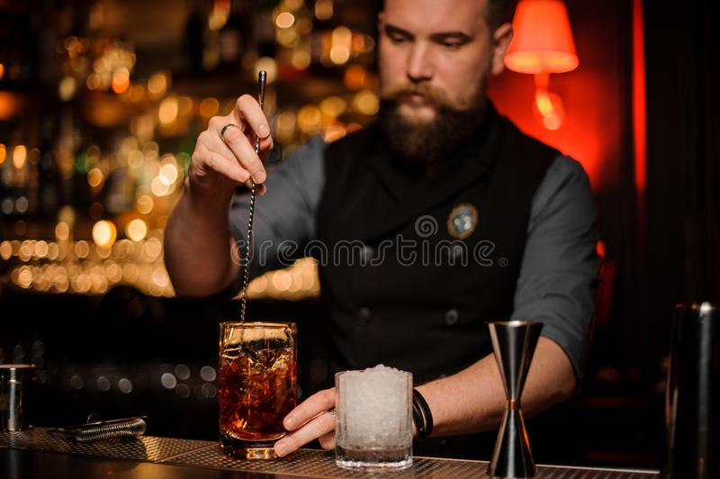 Barman stirring a delicious cocktail with a steel spoon in the measuring glass cup on the bar stand. In the blurred background royalty free stock images