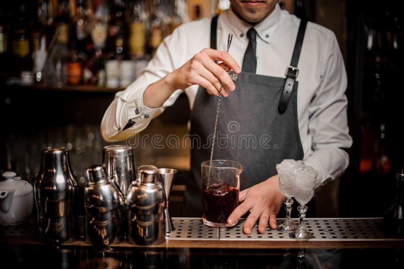Barman stirring fresh summer alcoholic cocktail in glass. Barman stirring a fresh and tasty summer alcoholic cocktail in glass on the bar counter royalty free stock photos