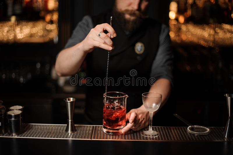Barman stirring a red cocktail with a steel spoon in the measuring glass cup. On the bar counter in the dark blurred background stock photography