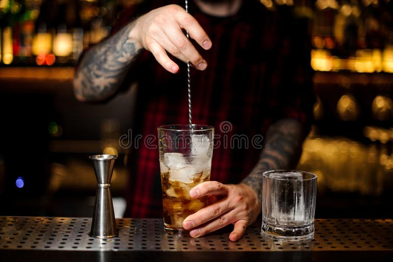 Barman stirring strong whiskey cocktail with ice cubes. Using a professional spoon on the bar counter royalty free stock photo