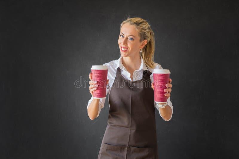 Barman tenant deux tasses de café sur le backround foncé photo libre de droits