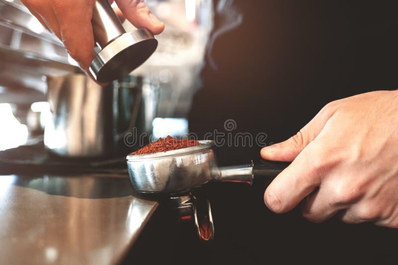 Barman tenant le support de café avec le cafè moulu dans une main et un bourreur dans une autre machine professionnelle proche de photographie stock