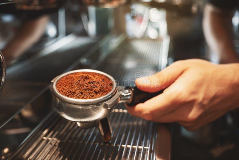 Barman tenant le support de café avec le cafè moulu près de la machine professionnelle de café préparant la boisson de café dans  images stock