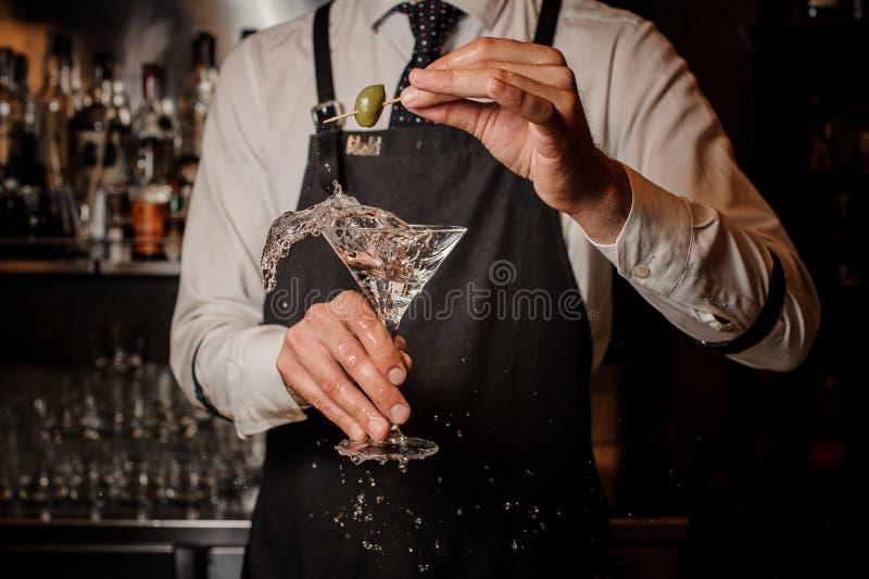 Barman tenant un éclaboussement du cocktail frais et fort de martini d'été de l'olive photo stock