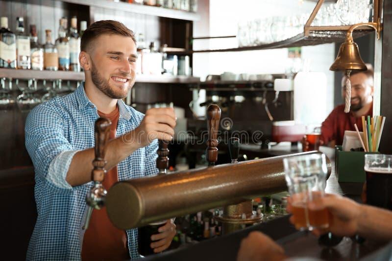 Barman travaillant au robinet de bière photographie stock