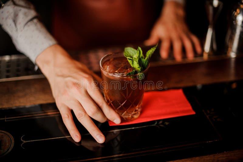 Barman trzyma koktajl z mennicą w jego ręce Żadna twarz fotografia royalty free