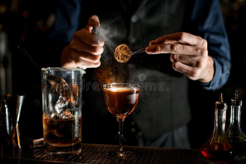 Barman trzyma pęsety z kawałkiem cytrusu na szkle i posypuje je obrazy royalty free