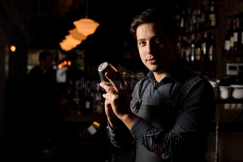 Barman trzyma potrząsacza w ciemnym barze obraz royalty free