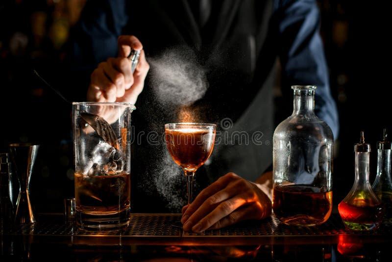 Barman trzyma szklankę drinka ręką i posypuje ją. zdjęcia royalty free
