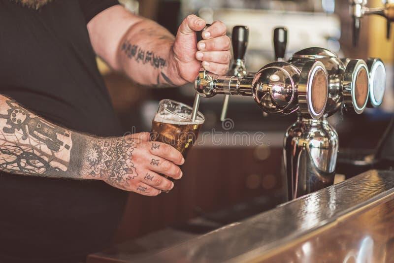 Barman versant la bière anglaise légère fraîche photo libre de droits