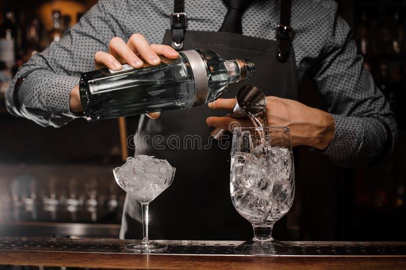 Barman versant la boisson alcoolisée dans un verre utilisant une petite mesure pour préparer un cocktail images stock