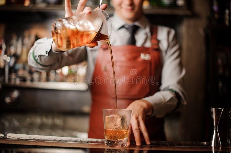 Barman w prętowym wewnętrznym robi alkoholu koktajlu fotografia royalty free