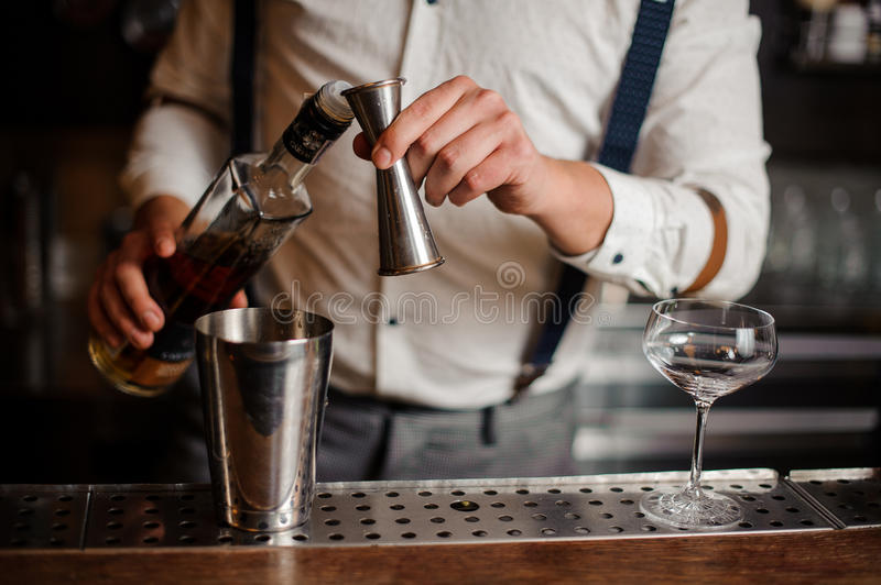 Barman in white shirt making alcohol coctail no face stock image