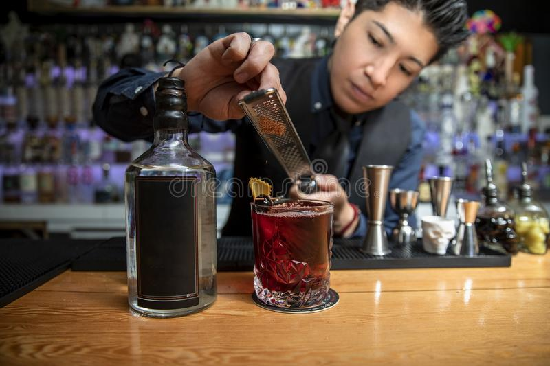 Barman working in a bar, preparing a cocktail stock images
