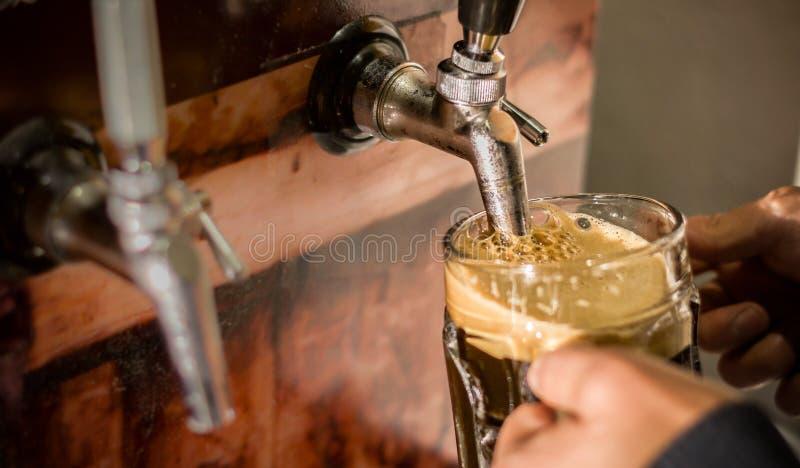 Barman wypełnia up z rzemiosła piwem pół kwarty szkło obrazy stock