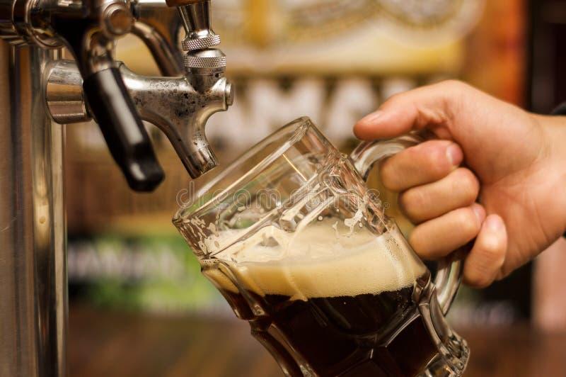 Barman wypełnia w górę zmroku z rzemiosła piwem pół kwarty szkło zdjęcie stock