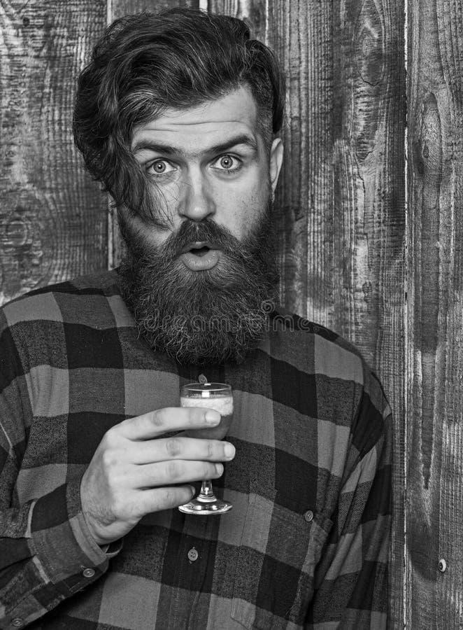 Barman z brodą i rozochoconą twarzą trzyma szkło z skrótem obrazy stock