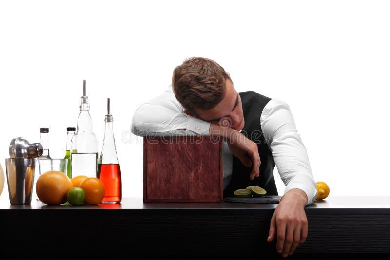 Barman zanudza przy prętowym kontuarem, plasterkami wapno, pomarańczami i cytrynami na białym tle, fotografia royalty free