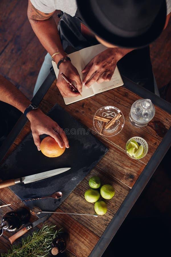 Barmannen die met het creëren van cocktails en neer het nemen experimenteren stock fotografie