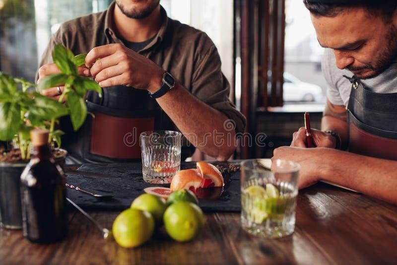 Barmannen die met het creëren van nieuwe cocktailsideeën experimenteren stock foto's
