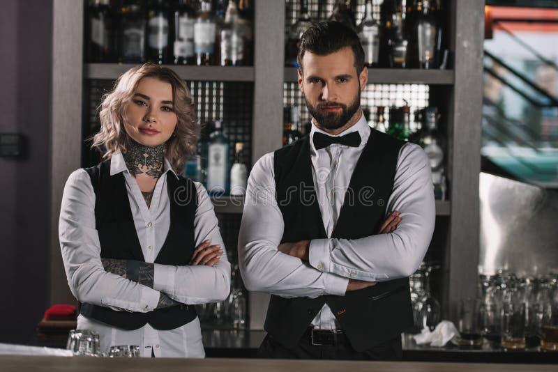 barmans féminins et masculins se tenant avec les bras croisés photo stock