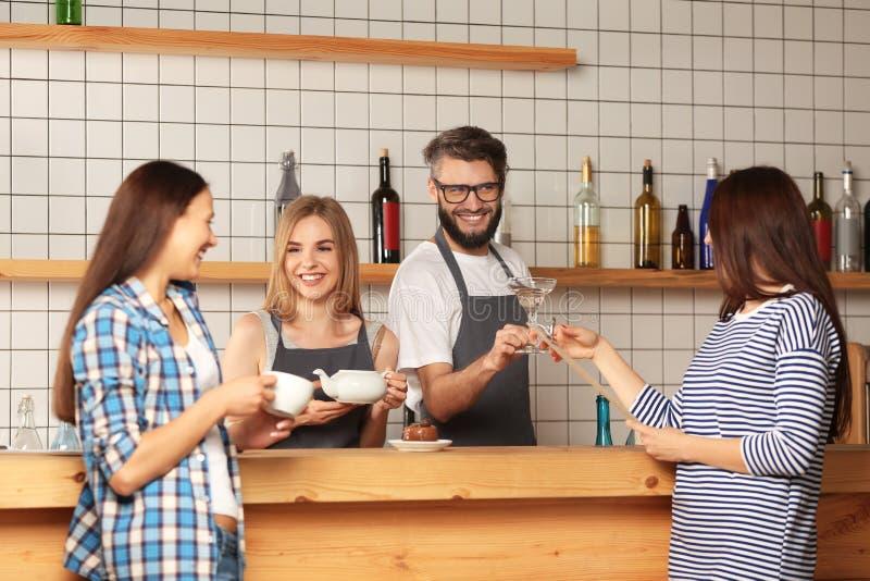 Barmans féminins et masculins travaillant avec les clients féminins dans la barre photos libres de droits