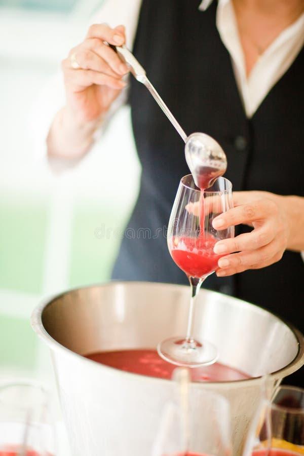 Barmanu dolewania koktajlu czerwona filiżanka na trzonie obraz stock