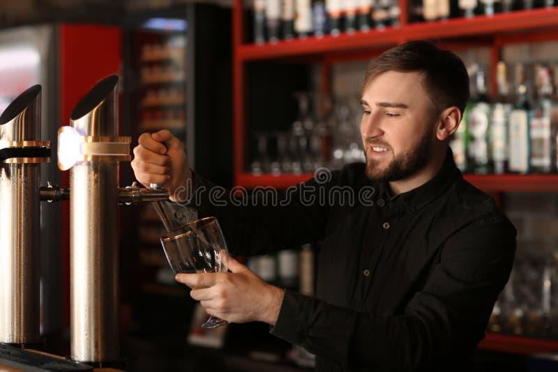 Barmanu dolewania piwo w szkło w barze obrazy stock