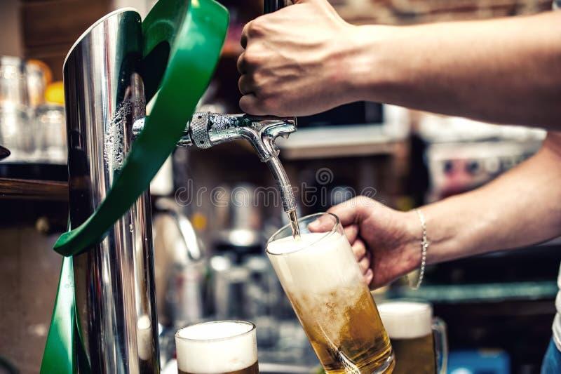 Barmanu piwowarstwo lub dolewanie łyknięcia piwo przy restauracją, bar obrazy royalty free