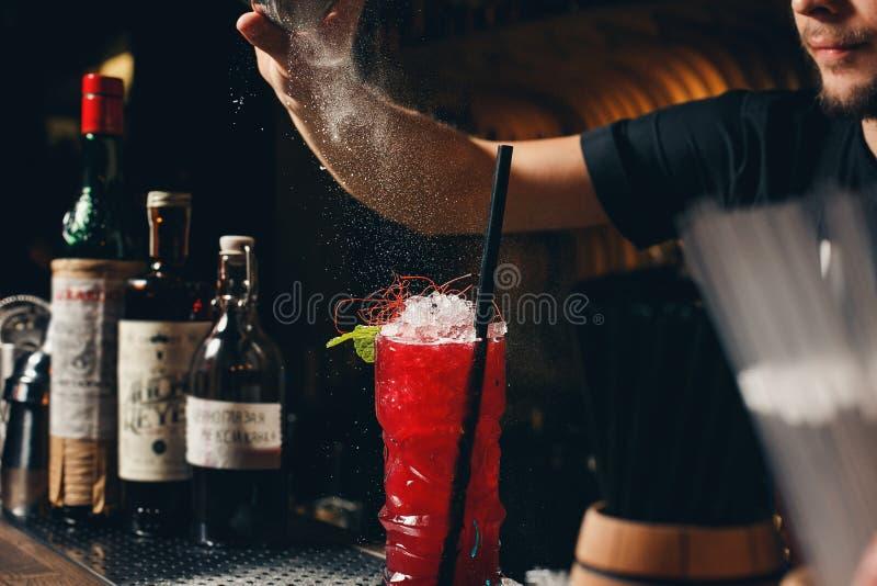 Barmanu ` s wręcza kropić sok z alkoholicznym napojem na ciemnym tle w koktajlu szkło wypełniającego fotografia stock
