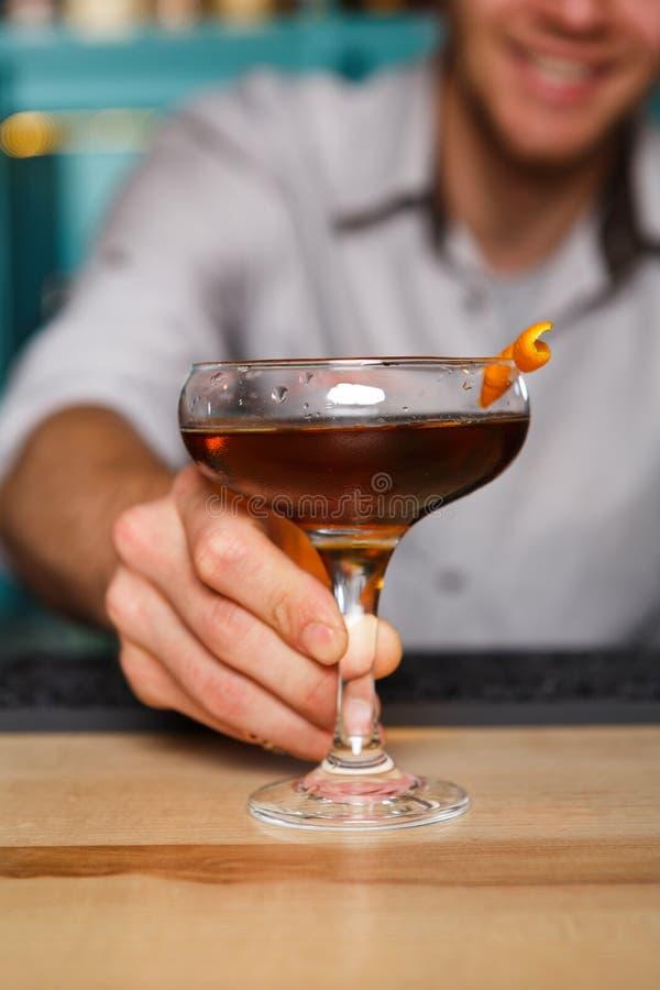 Barmixer bietet Alkoholcocktail in der Nachtclubbar an lizenzfreie stockbilder