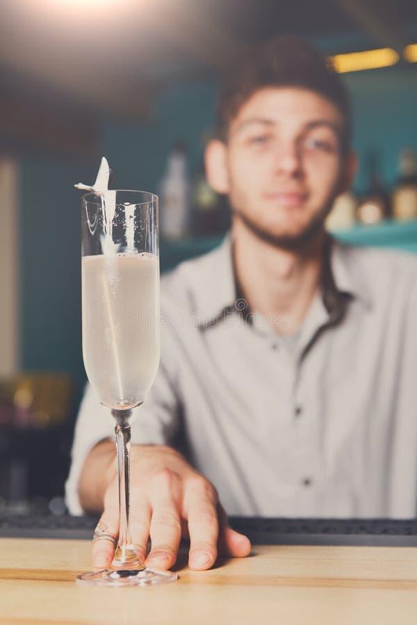 Barmixer bietet Champagnerglas in der Stange an stockfotografie