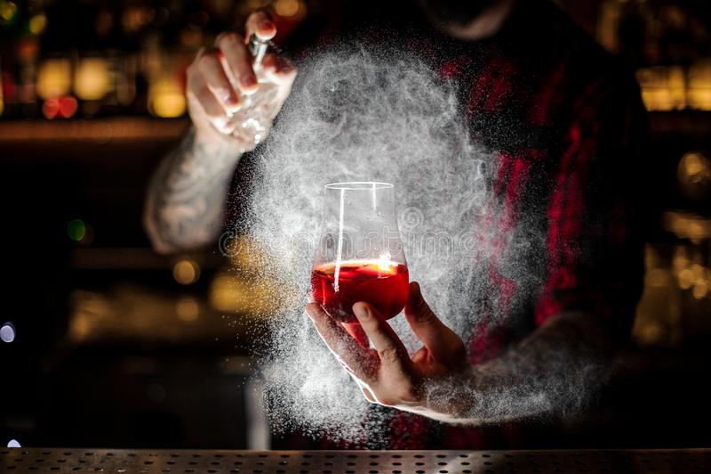 Barmixer, der auf das Sazerac-Cocktail mit orange Eifer sprüht lizenzfreie stockfotografie