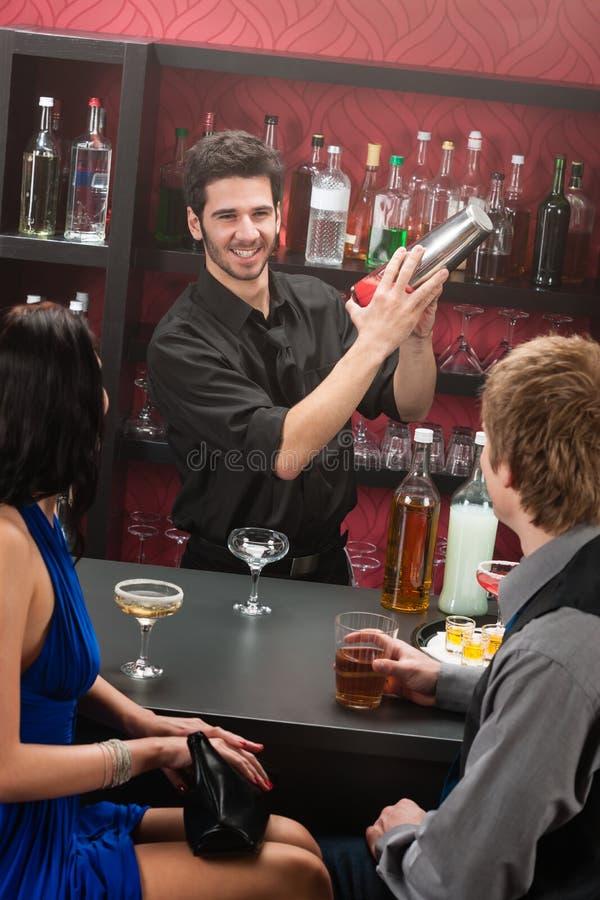 Barmixer, der die Cocktailfreunde haben Getränk rüttelt lizenzfreie stockfotos