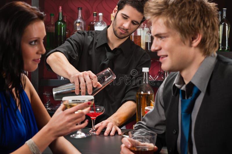 Barmixer, der die Cocktailfreunde haben Getränk rüttelt stockfotos