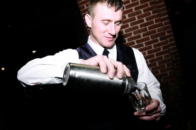 Barmixer, der ein Getränk gießt stockfotos