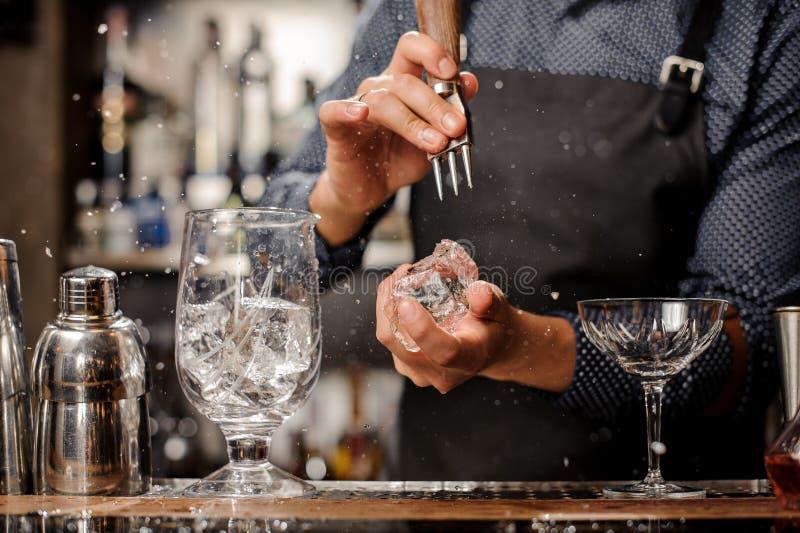 Barmixer, der ein großes Stück Eis für ein Cocktail zerquetscht stockbilder