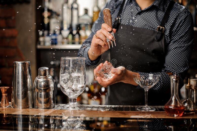 Barmixer, der ein großes Stück Eis für die Herstellung eines Cocktails zerquetscht stockfotos