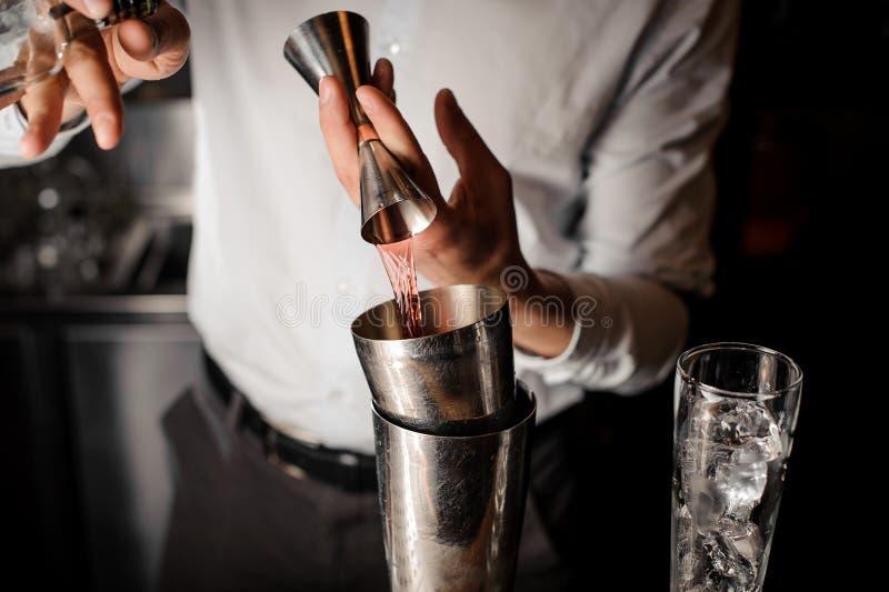 Barmixer, der ein transparentes rotes alkoholisches Getränk in den Stahlschüttel-apparat hinzufügt stockfotografie