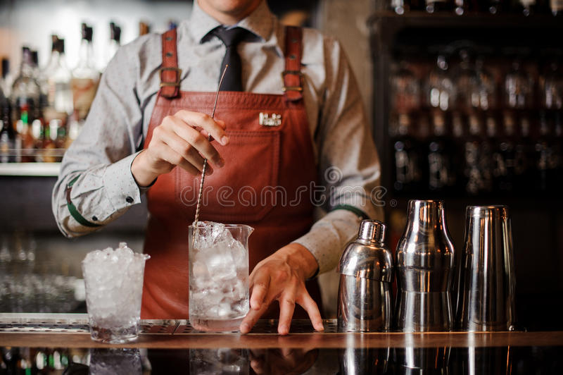 Barmixer, der heraus mischendes Eis des Cocktailglases mit einem Löffel abkühlt stockfotos