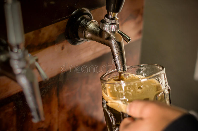 Barmixer, der mit Handwerksbier ein Pint-Glas auffüllt lizenzfreies stockfoto