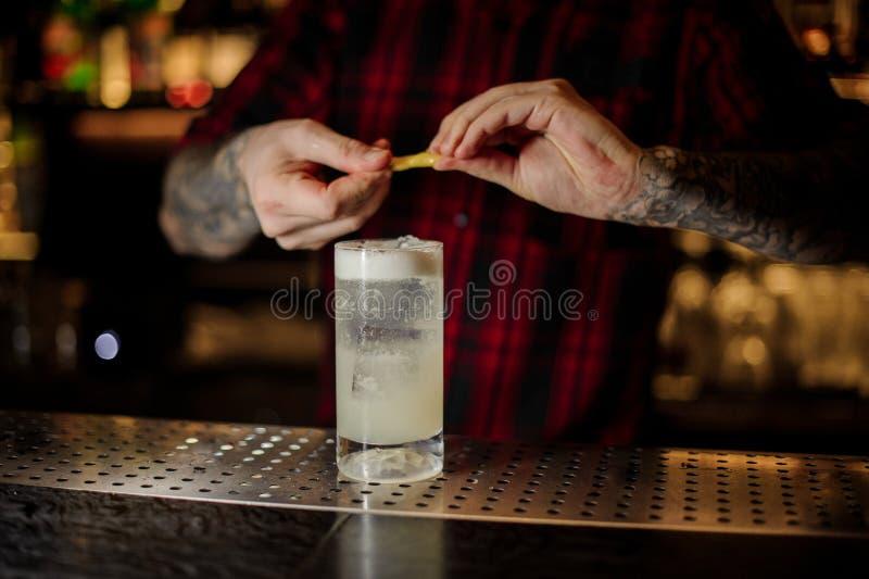 Barmixer, der Saft des orange Eifers einem Gin Fizz-Cocktail hinzufügt lizenzfreie stockbilder