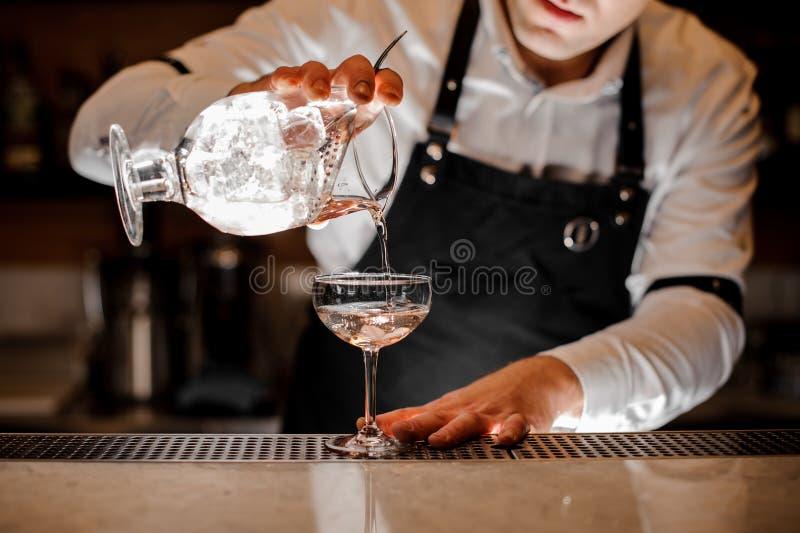 Barmixer, der Wodka in ein Cocktailglas im dunklen Licht hinzufügt stockbilder