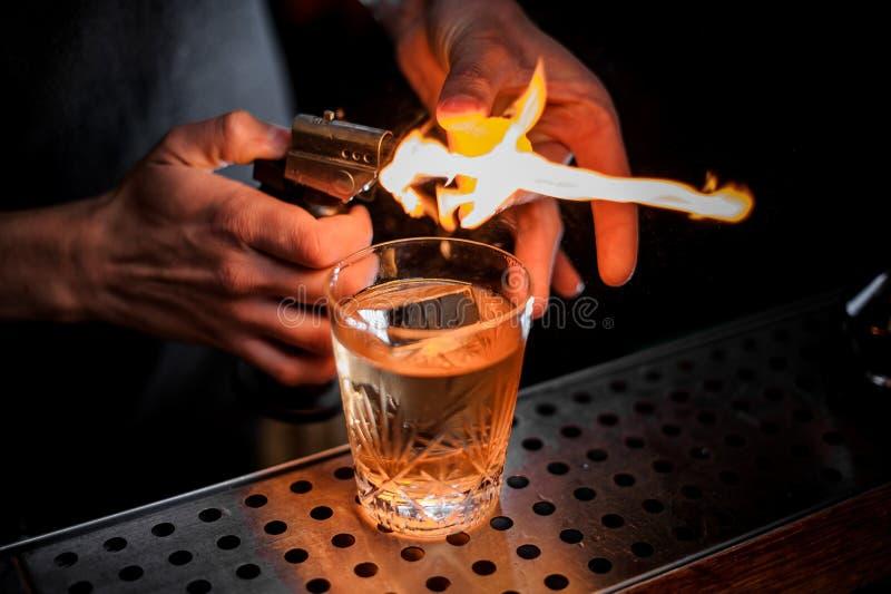 Barmixer feuerte den orange Eifer für das Hinzufügen er dem frischen alkoholischen Cocktail ab lizenzfreie stockbilder