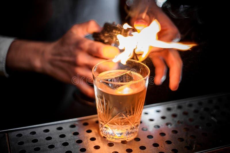 Barmixer feuerte den orange Eifer für das Hinzufügen er dem neuen alkoholischen Getränk ab stockfotos