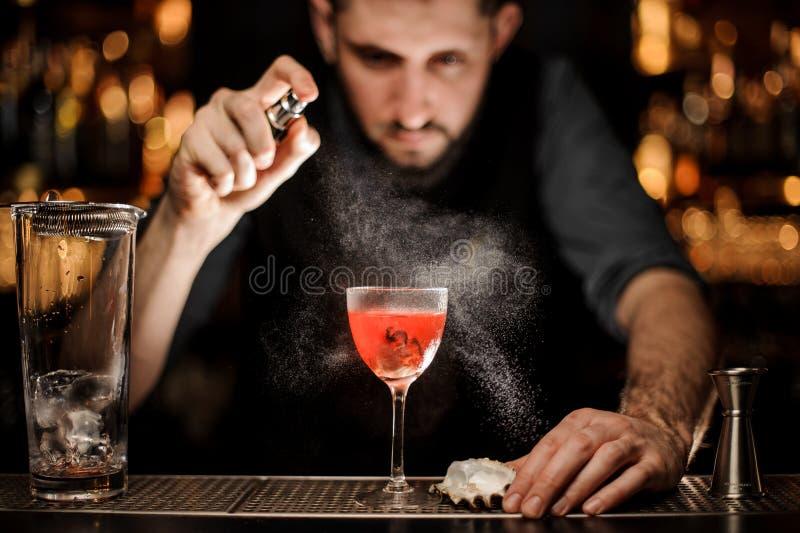Barmixer gießt ein Alkoholcocktail unter Verwendung des Sprühers lizenzfreie stockbilder