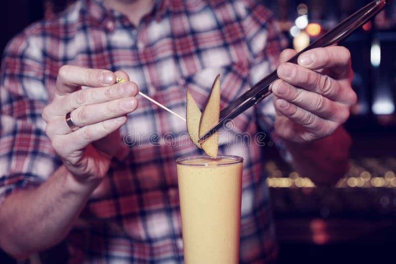 Barmixer verziert ein Cocktail mit Mango stockbild